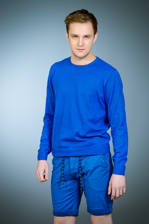 young man jeans: Smiling young man wearing casual clothes posing at studio. Mens beauty, fashion. Stock Photo