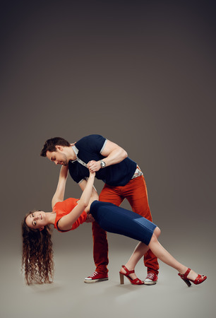 Couple of ypung people in love dancing. Studio shot. photo
