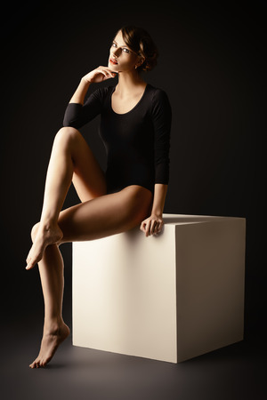 fitting in: Art portrait of a beautiful slim model in black fitting clothing. Beauty, fashion. Body care.