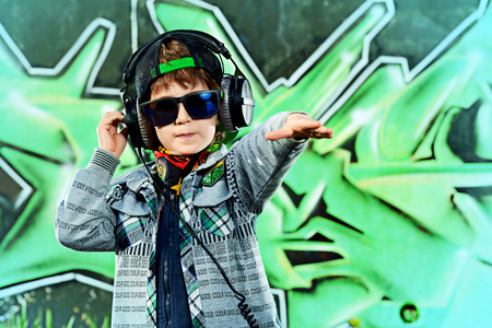 modern generation: Moda ni�o de 7 a�os en la calle. Fondo de la pintada. Generaci�n moderna.
