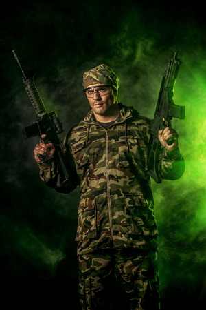 military men: Brave soldier in camouflage holding automatic rifle. Military. Stock Photo