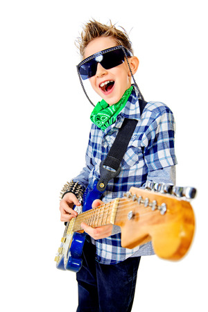 Modern boy teenager playing electric guitar and sing on a stage with expression.