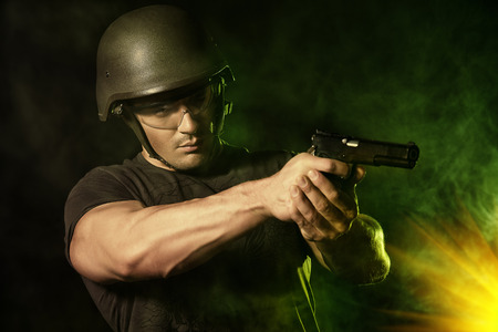 Brave soldier in camouflage and helmet holding a gun. Military. photo