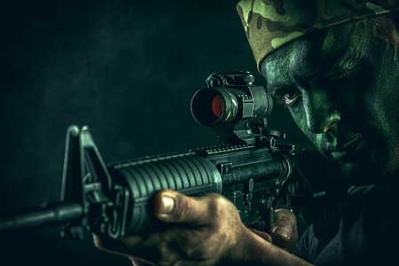 face paint: A soldier in war paint looks through the scope of automatic rifles.