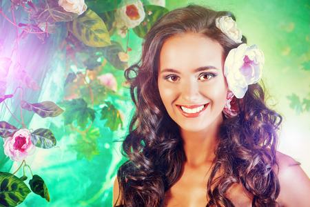 Happy beautiful brunette woman among summer plants and flowers. Beauty, fashion. Spa, healthcare. Tropical vacation. Stock Photo