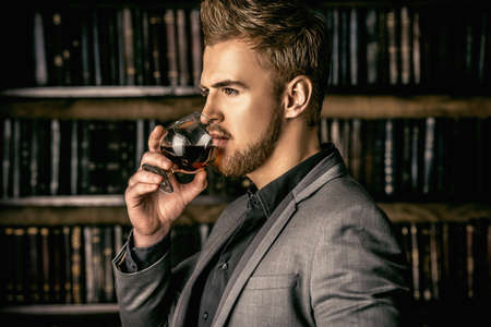 lifestyle: Elegant man in a suit with glass of beverage stands in vintage room. Fashion.