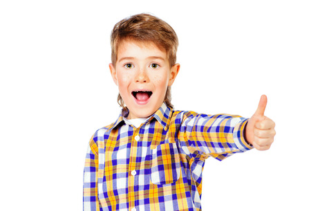 7 year old: Portrait of a cheerful 7 year old boy showing thumb. Copy space. Isolated over white. Stock Photo