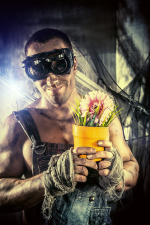 greenpeace: Strong muscular man coal miner holding a flower in a pot over dark grunge background. Mining industry. Greenpeace, environment protection.