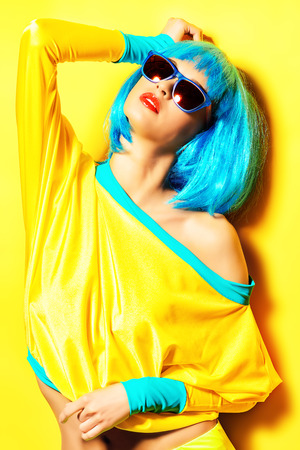 celadon blue: Bright glamorous girl in vivid clothes and a wig alluring over yellow background. Beauty, fashion. Cosmetics, hairtsyle. Optics, eyewear.