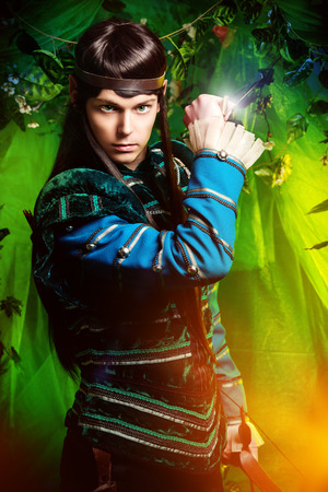 Beautiful warrior elf with a dagger in his hand in the magic forest. Fantasy. Fairy tale, magic. Stock Photo