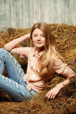 torn jeans: Pretty girl teenager in shirt and torn jeans posing on hay. Jeans fashion. Western style.