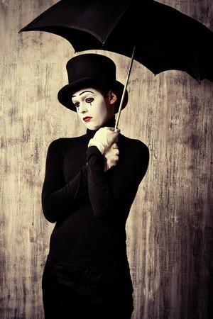 pantomima: Retrato de un mimo macho coloca bajo el paraguas que expresan tristeza y soledad. Grunge fondo.