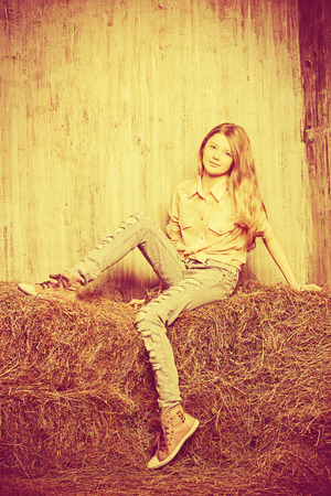 torn jeans: Pretty girl teenager in shirt and torn jeans posing on hay. Jeans fashion. Western style. Sepia.
