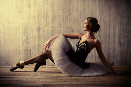 modern girls: Professional ballet dancer posing at studio over grunge background. Art concept.