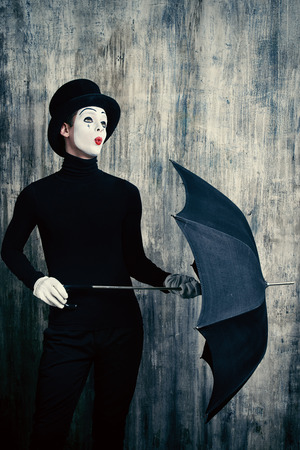 dramatic characters: Elegant male mime artist in top hat posing with umbrella by a grunge wall.