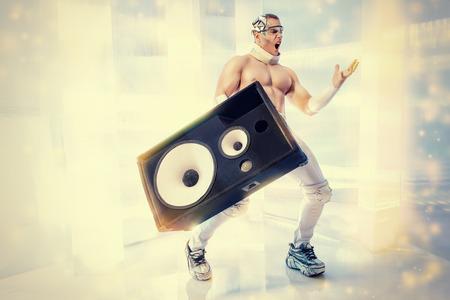 disco speaker: Futuristic muscular man dancing with huge music speakers on a luminous transparent background. Music, technology. Futuristic DJ. Stock Photo
