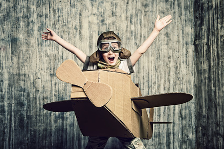 history: Little dreamer boy playing with a cardboard airplane. Childhood. Fantasy, imagination.