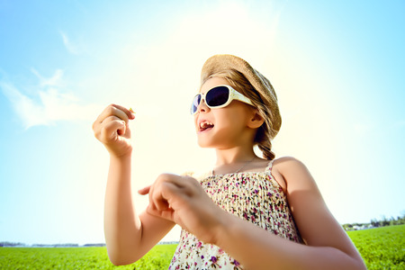 Pretty little girl blows bubbles on a meadow in summer day. Happy childhood. Blue sky. photo