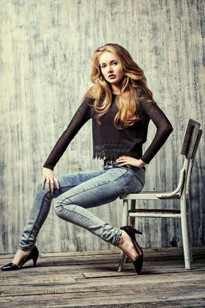 women jeans: Beautiful blonde girl in jeans clothes posing by the grunge wall. Fashion.