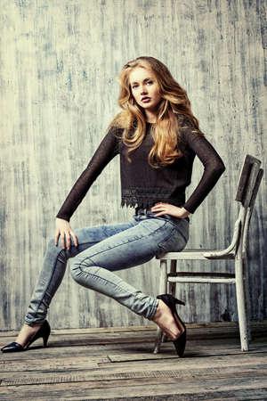 in jeans: Hermosa chica rubia en ropa de jeans posando junto a la pared del grunge. Moda.