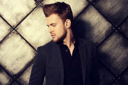 時尚: 時尚打出一個英俊的男子在黑色西裝,在構成工作室。男士美容,時尚。