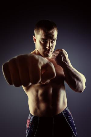 pelea: Hombre musculoso fuerte lucha con los puños. Artes marciales. Peleas, boxeo. Culturismo. Fondo negro.