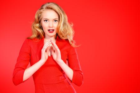 rubia: Encantadora mujer joven sonriente en vestido rojo y con el pelo rizado rubio. Belleza, la moda. Cosm�ticos, maquillaje. Fondo rojo. Foto de archivo