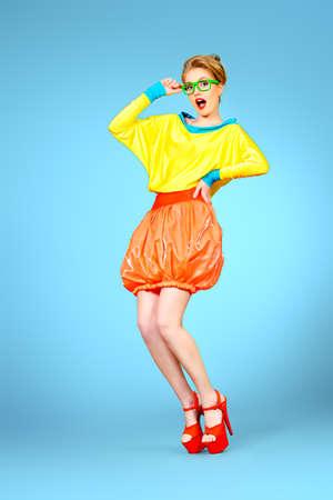 Full längd porträtt av en glamorös modell poserar i levande färgglada kläder och glasögon. Bright mode. Optik, glasögon. Studio skott. Stockfoto