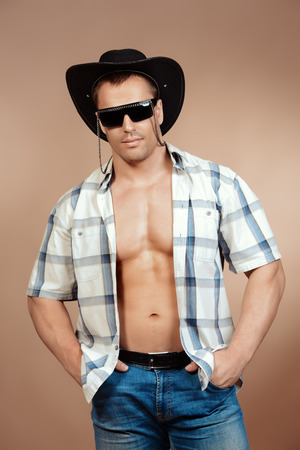 sexy cowboy: Portrait of a sexy cowboy man posing at studio. Western style. Denim, jeans. Stock Photo