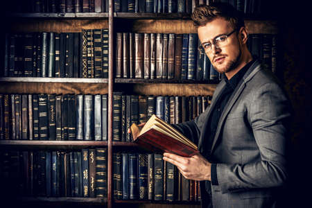 business book: Handsome well-dressed man stands by bookshelves in a room with classic interior. Fashion. Stock Photo