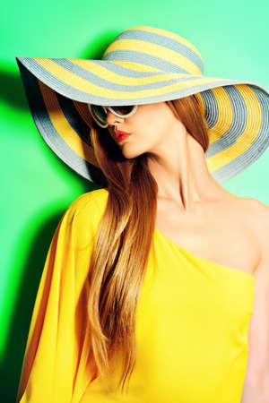 kapelusze: Portret pięknej modnej pani w jasnym żółtym sukienka stwarzających na zielonym tle. Urody, mody koncepcji. Kolory lata. Zdjęcie Seryjne