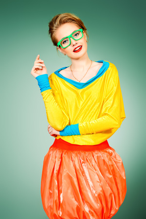eyewear fashion: Glamorous fashion model posing in vivid colourful clothes and glasses. Bright fashion. Optics, eyewear. Studio shot.