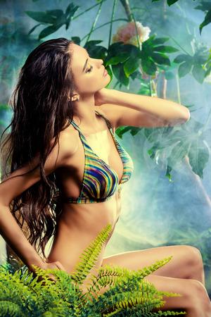 femme brune sexy: Belle femme sexy en bikini parmi les plantes tropicales. Beauté, mode. Spa, soins de santé. Voyage dans les tropiques. Banque d'images