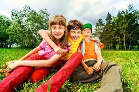 group of persons: Three joyful children sitting on the grass in the park. Summer.
