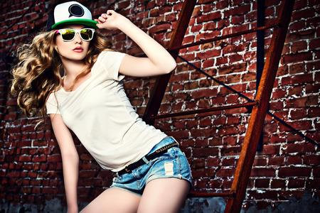 juventud: Chica moderna hermosa cerca de la pared de ladrillo. Estilo de la Juventud. Disparo de moda. Foto de archivo