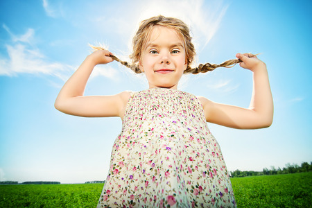 5 year old girl: Portrait of a cute 5 year old girl on a blue sky background. Happy childhood.