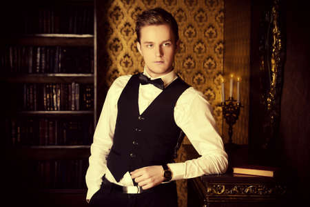 respectable: Young handsome man in evening suit stands by the fireplace in a room with classic vintage interior. Fashion.