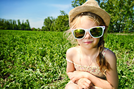5 year old girl: Cute little girl on a meadow in summer day. Happy childhood. Stock Photo