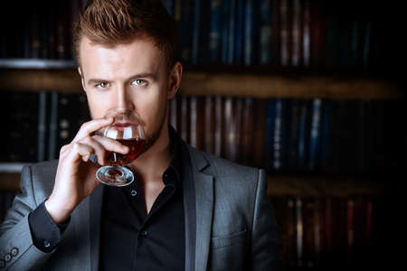riches: Elegant man in a suit with glass of beverage stands in vintage room. Fashion.