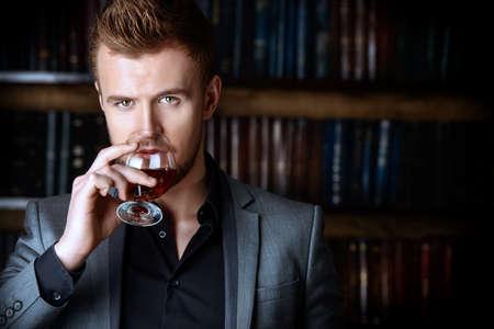 traje: Hombre elegante en un traje con un vaso de bebida se coloca en sitio de la vendimia. Moda. Foto de archivo