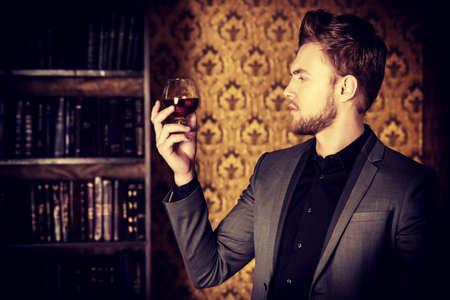 whisky: Homme élégant dans un costume avec verre de boissons et de cigares dans la chambre vintage. Mode.