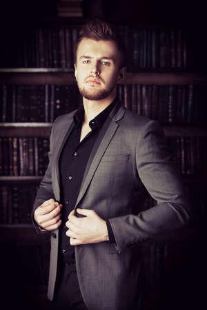 bel homme: Handsome homme bien habill� se en tient � des �tag�res dans une chambre avec un int�rieur classique. Mode. Banque d'images