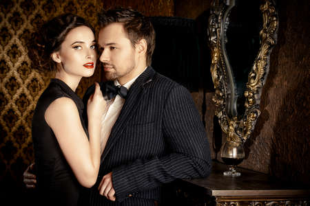 chic woman: Beautiful man and woman in elegant evening clothes in classic vintage apartments. Glamour, fashion. Love concept.
