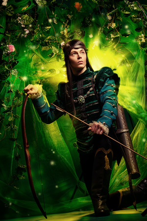magical forest: Portrait of a male elf with a bow and arrows in a magical forest.