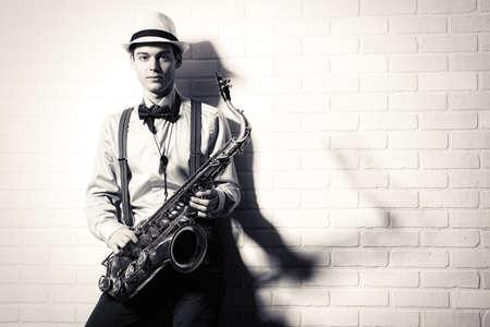 musico: Retrato en blanco y negro de un elegante músico de pie con su saxofón por la pared de ladrillo. Arte y música. Musica Jazz.