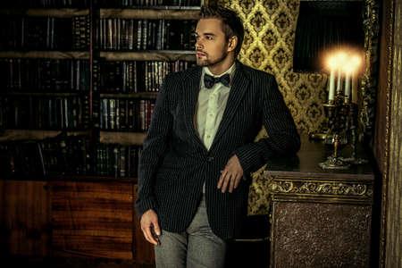beau jeune homme: Beau jeune homme élégant dans des appartements classiques vintage. Mode. Luxe.
