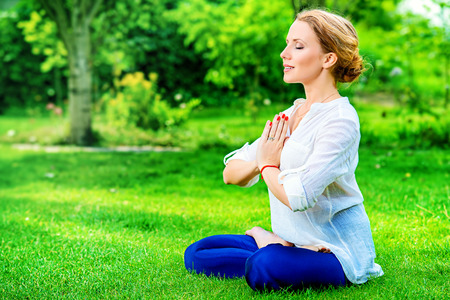 body and soul: Beautiful young woman doing yoga in the summer park. Healthy lifestyle. Yoga. Lotus pose.