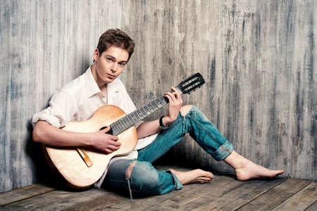 gitara: Romantyczny młody mężczyzna gra na gitarze akustycznej, siedzi na drewnianej podłodze