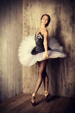 Professional ballet dancer posing at studio over grunge background. Art concept. photo