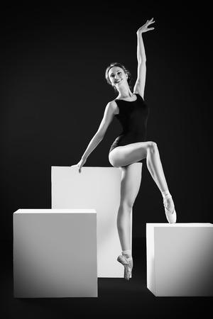 turnanzug: Elegante schöne Ballett-Tänzerin in schwarz Ballett-Trikotanzug posiert im Studio auf weißem Würfel. Kunstkonzept.